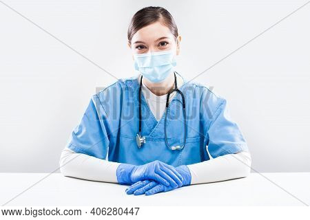 Young Female Caucasian Nhs General Practitioner Sitting At Office Desk,wearing Blue Uniform,protecti