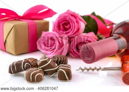Valentine's Day Concept. Delicious Chocolate Pralines, Wine Bottle, Corkscrew, Pink Roses And Gift B