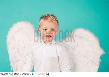Portrait Of Little Blond Angel Boy. Child With Angelic White Dress. Toddler Boy Wearing Angel Costum