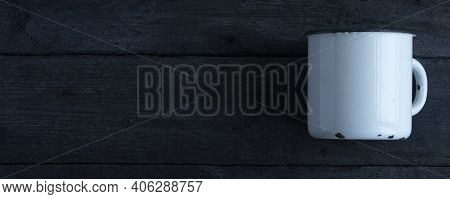 White Empty Enamel Mug, On A Wooden Background.