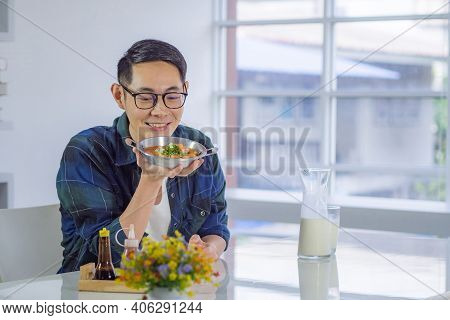 Young Man's Wearing Glasses Sitting And Looking At The Fried Egg Served On A Pan With Colorful Toppi
