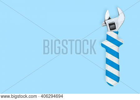 Adjustable Metal Wrench. Background Made Of A Metal Adjustable Wrench With A Rubber Striped Handle.