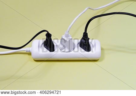 Side View Of The White And Black Electrical Wires From The Extension Cord Stuck In The Adapter. A Me
