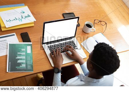 Overhead view of african american woman using laptop while working from home. staying at home in self isolation in quarantine lockdown