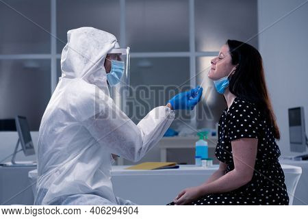 Caucasian male medical worker wearing protective clothing taking swab of masked female patient. healthcare, medical research technology and hygiene during coronavirus covid 19 pandemic.