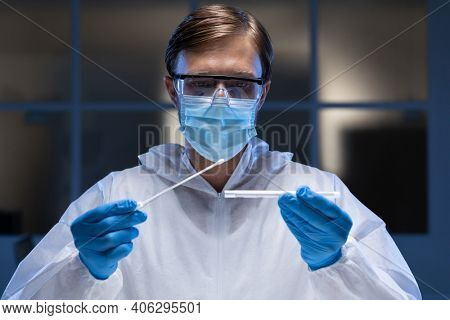 Caucasian male medical worker wearing protective clothing and face mask inspecting swab in lab. healthcare, medical research technology and hygiene during coronavirus covid 19 pandemic.