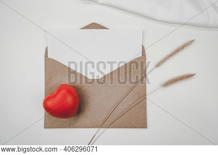 Blank White Paper Is Placed On Open Brown Paper Envelope With Red Heart, Bristly Foxtail Dry Flower,