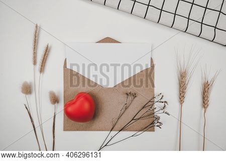 Blank White Paper Is Placed On Open Brown Paper Envelope With Red Heart, Many Kinds Of Dried Flowers