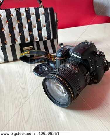 Perm, Russia, June  2020. Photo Camera Nikon D750 And Striped Bag On Table In Room