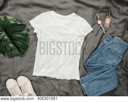 Fashionable Look With White Empty T-shirt, Jeans And White Sneakers. Top View Of White Blank T-shirt