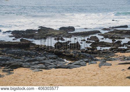 Black Rocks On Shoreline With Clean Beach Sand