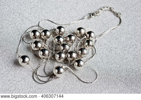 Women's Jewelry In The Form Of Silver Beads On A Silver Thread With A Clasp, Photographed Against A