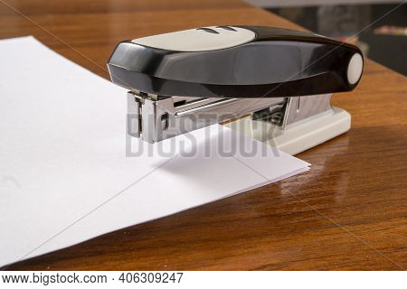 A Stack Of White Paper Is Stapled Together With A Stapler
