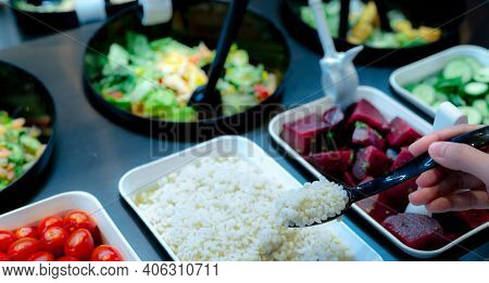 Hand Holding Spoon With Boiled Job's Tears At Salad Bar. Salad Bar Buffet At The Restaurant. Fresh S