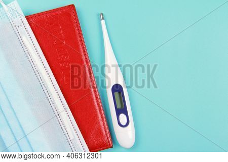 Passport, Thermometer, Disposable Medical Mask On A Blue Background.global Problems And The Closure