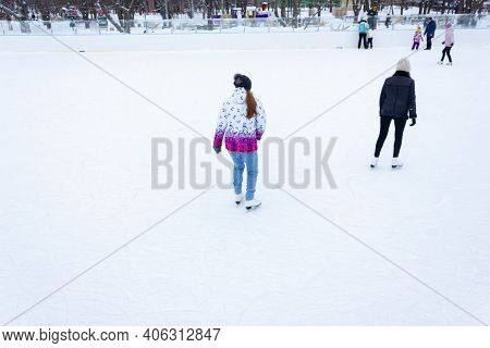Close-up Of Girls Ice Skating In Winter On An Outdoor Ice Rink. Ice Skates Of Two Friends Ice Skatin