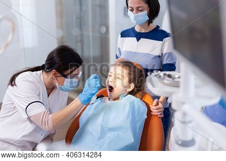 Dentist Wearing Gloves During Cavity Procedure On Little Girl Sitting On Dental Chair. Dentistry Spe