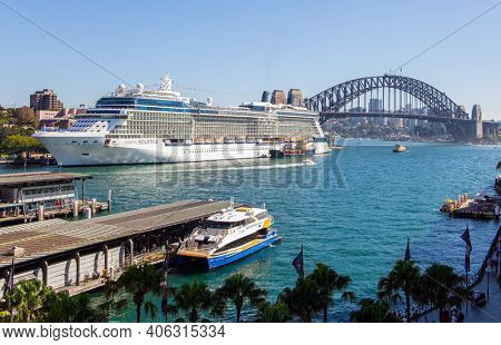Sidney, Australia. The famous Sydney Harbor. Boat trip on a tourist boat along the picturesque shores of the port. Huge white ocean liner and small tourist boats at the quays