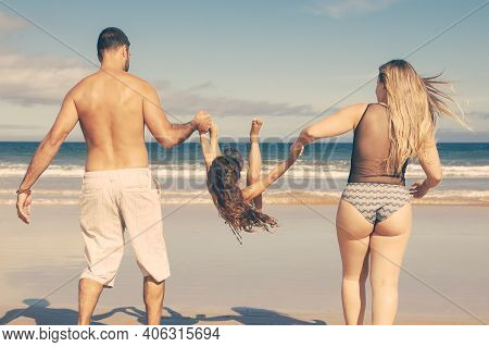 Parents And Little Girl Wearing Swimsuits, Walking On Golden Sand To Water. Girl Holding Parents Han