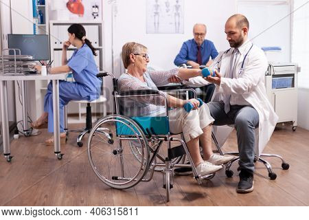 Handicapped Patient Getting Help From Physical Therapist. Elderly Invalid Patients In Hospital Follo