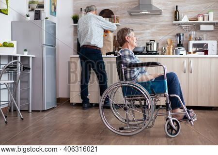 Paralysed Senior Woman In Wheelchair Feeling Unhappy Sitting In The Middle Of Kitchen While Husband