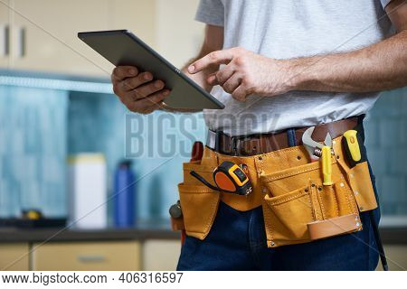 Cropped Shot Of Young Repairman Wearing A Tool Belt With Various Tools Using Digital Tablet While St