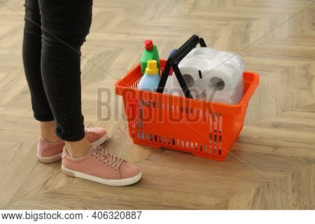 Woman And Shopping Basket With Household Goods On Wooden Floor, Closeup