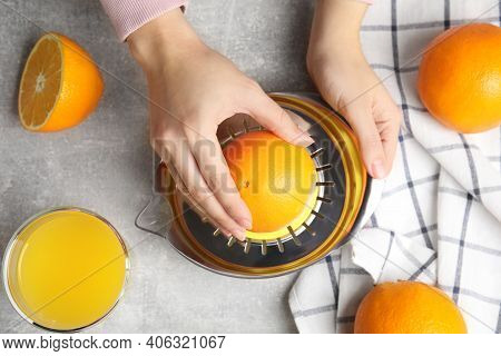 Woman Squeezing Orange Juice At Grey Table, Top View