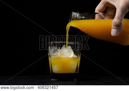 The Juice Is Poured Into A Glass With Ice On A Black Background. A Male Chicken Pours Juice From A B