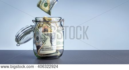 Money In Cash Box Over Gray Background With Copy Space. Donations Charity Concept. Dollars With Glas