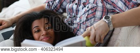 Portrait Of Smiling African American Young Woman Reading Interesting Book And Laying. Happy Middle-a
