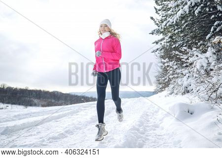 A Woman Runs In The Snow In The Winter Mountains. Sports, Fitness - Inspiration And Motivation. Woma