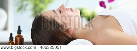 Close-up Of Young Beautiful Woman Laying On Massage Table In Spa Salon. Relaxed Lady Smiling And Fee