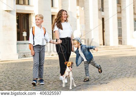 Happy Family Walking With Dog In City Street. Stylish Mother And Kids Having Fun With Their Dog Outd