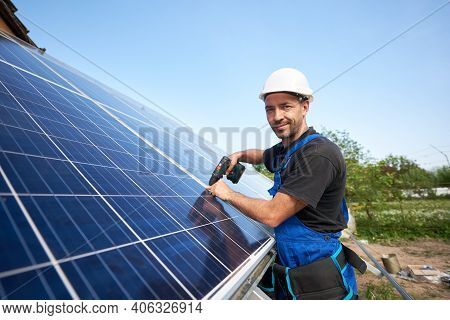 Smiling Technician Mounting Solar Panel To Metal Platform Using Electrical Screwdriver On Blue Sky C