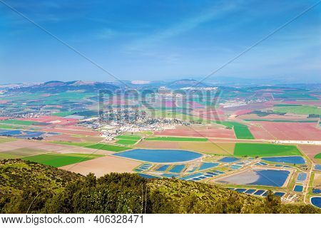 Israel. Jezreel Valley in the Lower Galilee. Picturesque agricultural fields cover the entire valley. The land in the Jezreel Valley is divided between kibbutzim, moshavim and Arab villages.