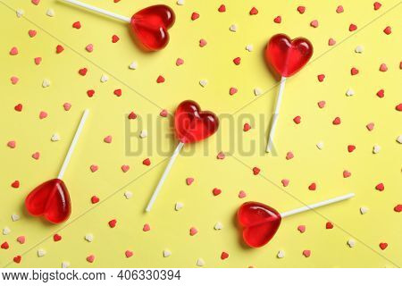 Sweet Heart Shaped Lollipops And Sprinkles On Yellow Background, Flat Lay. Valentine's Day Celebrati