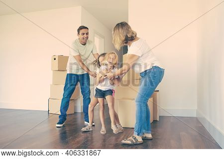 Excited Happy Girls Tickling Each Other And Laughing. Happy Family Couple And Two Kids Having Fun To