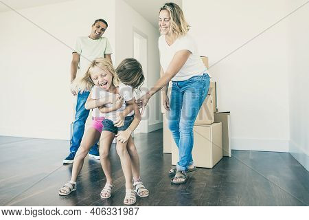 Excited Girls Tickling Each Other And Laughing. Happy Family Couple And Two Kids Having Fun While Mo
