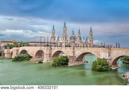 Zaragoza, Spain. View Of Historic Puente De Piedra Bridge. Long Exposure Shot With Hdr Effect