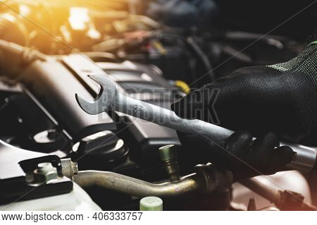 The Mechanic Hand Wearing Black Gloves Holding Open-end Wrench With A Sunlight And Engine Blurred On