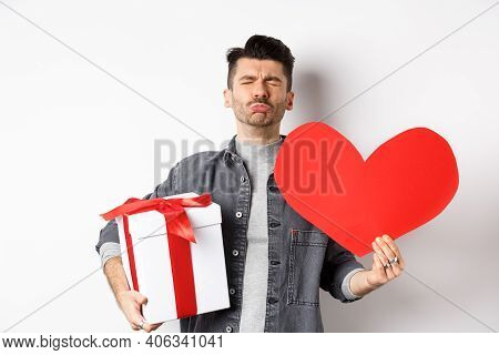 Sad And Heartbroken Man Being Rejected, Crying And Holding Red Heart With Gift Box, Breakup On Valen