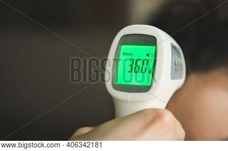 A Non-contact Digital Infrared Thermometer Recorded The Normal Body Temperature. Prevention Of Coron