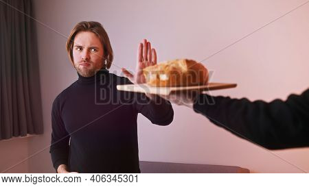 Young Caucasian Man Gluten Intolerant Refusing To Take Loaf Of Bread. High Quality Photo