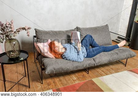 Young Woman With Red Hair Is Lying On Couch And Reading Book. Quiet Leisure At Home With Book In Coz