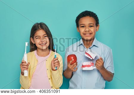 Multi-ethnic Kids Holding Manual And Electric Ultrasonic Toothbrushes. Oral Hygiene Concept To Child