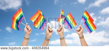 lgbt, same-sex relationships and homosexual concept - close up of male hands wearing gay pride awareness wristband holding rainbow flags over blue sky and clouds background