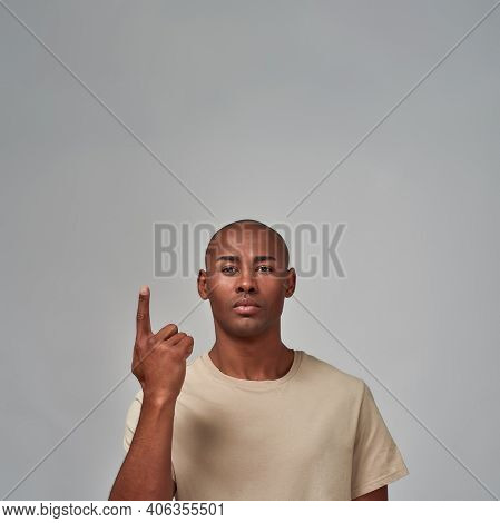 Waist-up Photo Of A Self-assured Citizen Directing One Finger On The Right Hand Upward