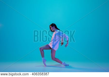Stylish. Young And Graceful Ballet Dancer Isolated On Blue Studio Background In Neon Light. Art, Mot