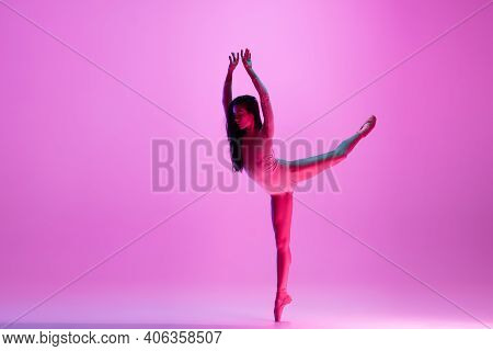 Flying, Freedom. Young And Graceful Ballet Dancer On Pink Studio Background In Neon Light. Art, Moti